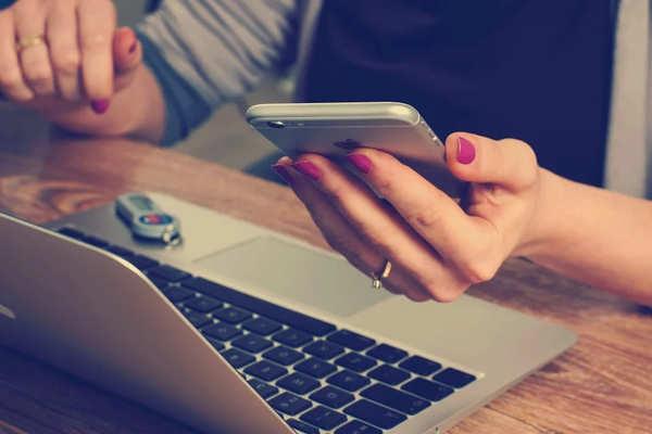 パソコンとスマートフォンを見ている人